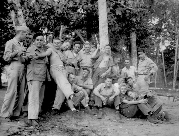"The pilots of VF-21 at ""Point Easy"" on Punam in the Solomon Islands. The author is center front, shirtless, reaching for a beer."