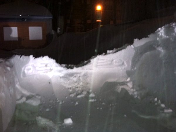 Imprint from front grill and headlights left in snow after removing car.